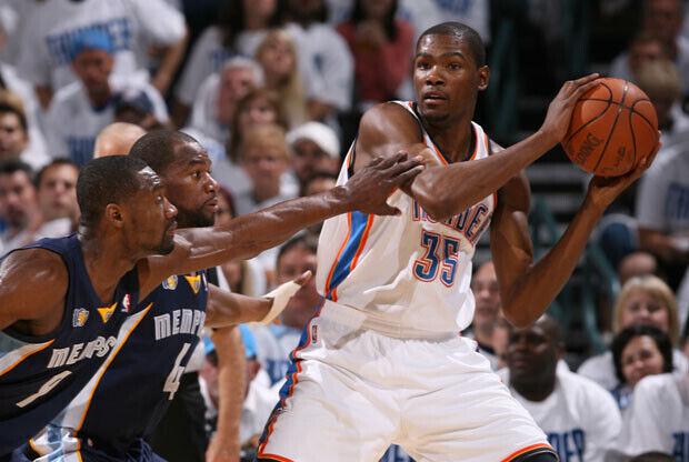 Kevin Durant, de los Thunder, buscando el pase ante dos defensores de los Grizzlies./ Getty Images