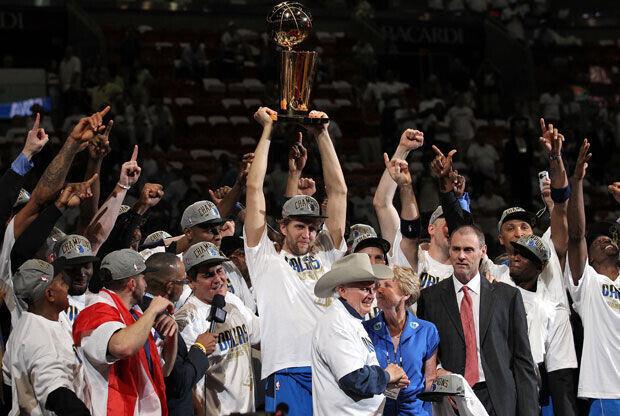 Dirk Nowitzki, rodeado por todo sus compañeros, con el trofeo de campeones de la NBA 2011./Getty