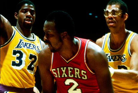 Moses Malone, defendido por Kareem Abdul Jabbar y Magic Johnson./Getty