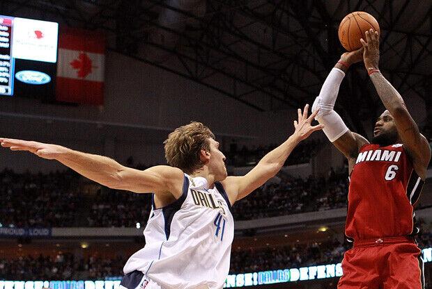 Dirk Nowitzki puntea el tiro a LeBron James./ Getty