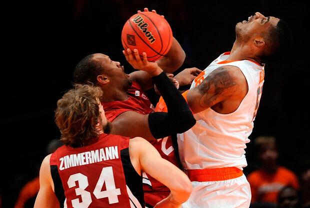 Fab Melo, jugador de Syracuse Orange, lucha por un balón ante dos jugadores de Stanford Cardinal./ Getty