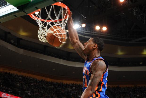 Iman Shumpert,de New York Knicks, realiza un mate delante de Kevin Garnett, Celtics./ Getty