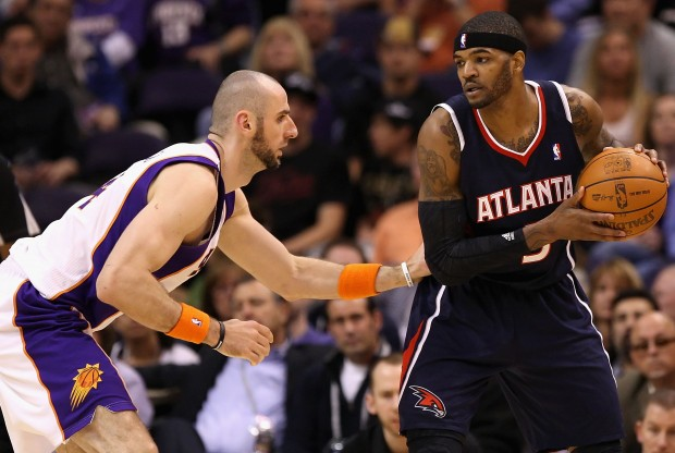 Marcin Gortat defiende a Josh Smith./ Getty Images