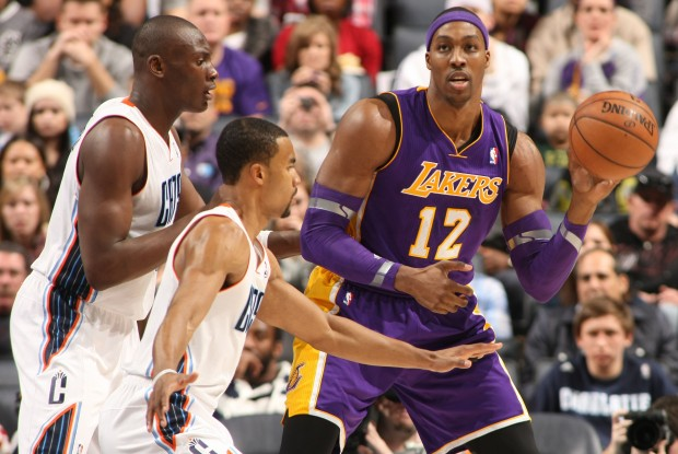 Dwight Howard busca el pase ante la defensa de Bismack Biyombo y Ramon Sessions./ Getty Images