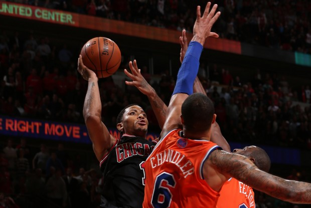 Derrick Rose lanza ante Tyson Chandler y Raymond Felton./ Getty Images