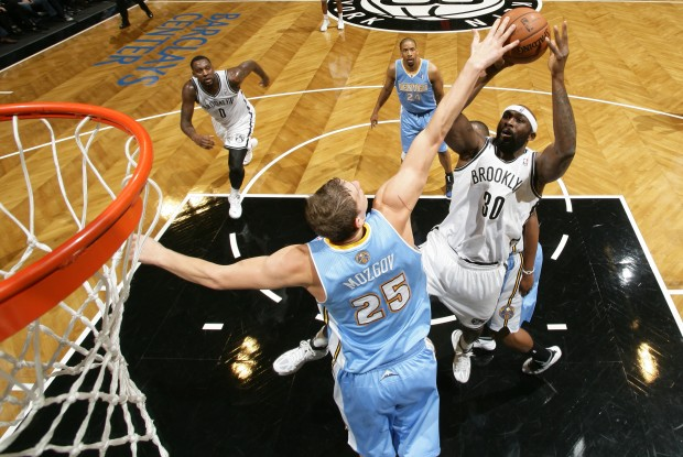 Timofey Mozgov tapona a Reggie Evans./ Getty Images