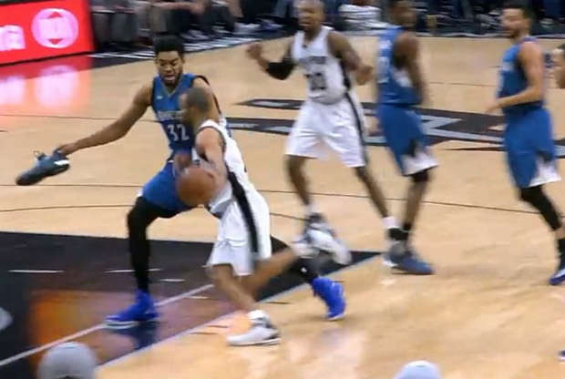 Karl-Anthony Towns defendiendo con una zapatilla en la mano