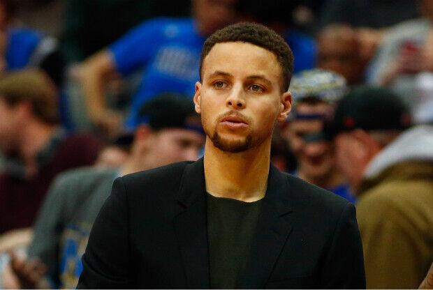 Stephen Curry lesionado viendo un partido de NBA