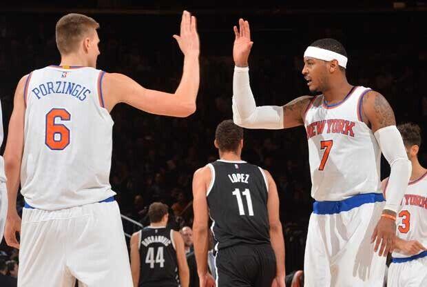 Carmelo Anthony y Kristaps Porzingis chocan sus manos